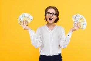 eine Frau hält zwei Bündel aus Geldscheinen in den Händen
