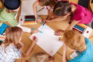 Kinder malen zusammen an einem Bild