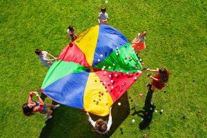kinder spielen draußen gemeinsam mit einem tuch und baellen