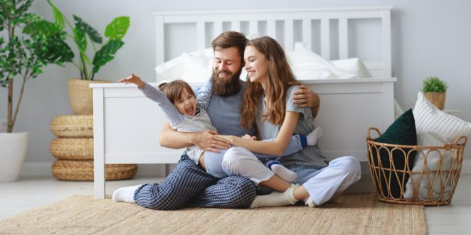 Eltern sitzen auf Boden und kuscheln mit Kind