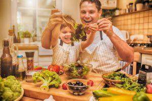 Vater und Sohn bereiten zusammen einen Salat zu