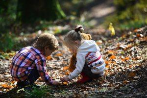 Kinder sitzen zusammen im Wald