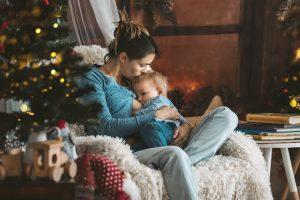 mutter stillt ihr baby in einem gemuetlichen sessel neben dem weihnachtsbaum