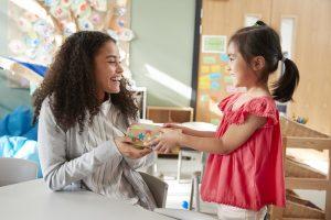 kleines Mädchen überreicht der Erzieherin ein Geschenk