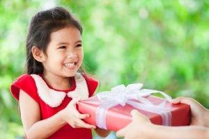 maedchen bekommt ein geschenk ueberreicht