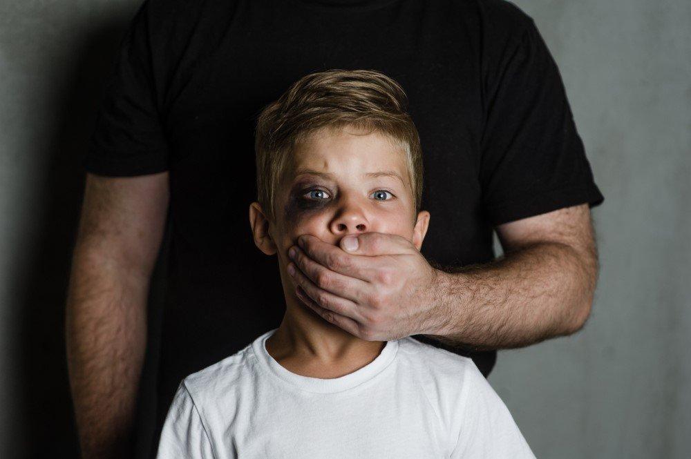 Mann hält geschlagenem Kind den Mund zu
