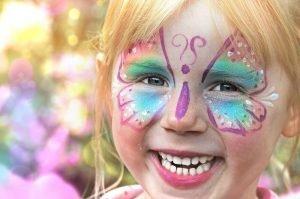geschminktes Kind mit einem Schmetterling im Gesicht
