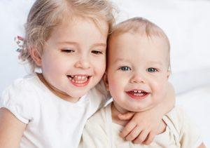 Kleinkind und Baby lächeln und lachen