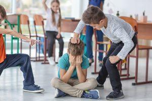 ein Schüler schlägt ein am Boden sitzendes Kind