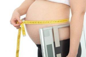 Schwangere Frau misst Bauch mit Waage in der Hand