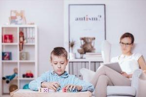 Ergotherapeutin beobachtet einen Jungen bei einer Aufgabe