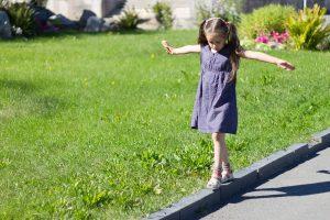Kind balanciert über einen Bordstein