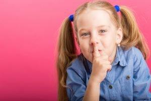 Mädchen hält ihren Finger auf die Lippen