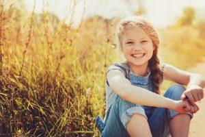 lächelndes Kind sitzt im Gras