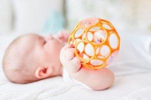 Baby greift mit einer Hand nach einer Rassel