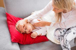 Mutter fühlt Temperatur des Kindes