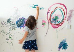 Kleines Mädchen malt an die Wand