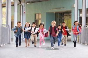 Kinder laufen einen Flur entlang