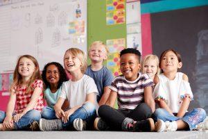 eine gruppe von kindern sitzt auf dem boden