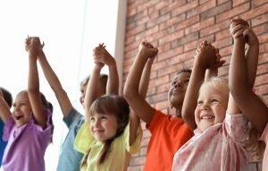 eine gruppe von kleinen kindern reisst die arme in die luft