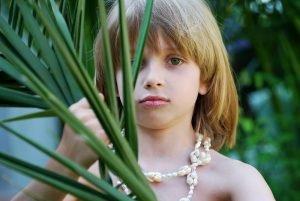 ein junge traegt eine halskette mit muscheln