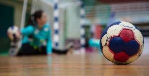 ein handball im fokus vor einem tor