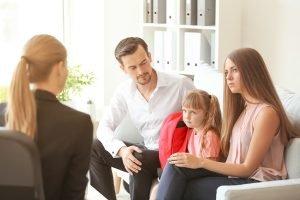 Elternpaar sitzen mit Tochter bei der Direktorin