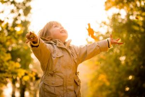 Kind spielt im Herbst draußen