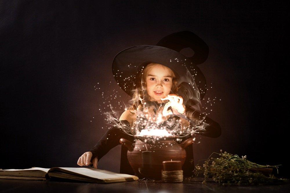 Kind als Hexe vor einem Zauberkessel