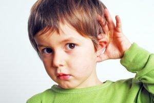 Kind hält sich die Hand ans Ohr
