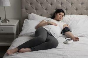 schwangere liegt im bett und misst ihren blutdruck