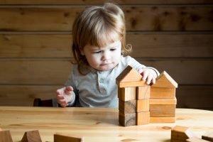 kleines Kind baut Häuser aus Holzbauklötzen