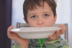 hungriges Kind zeigt einen leeren Teller
