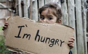 """Kind hält ein Schild mit der Aufschrft """"I'm hungry"""" in den Händen"""