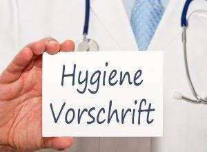 Arzt hält Schild mit der Aufschrift Hygienevorschrift in der Hand
