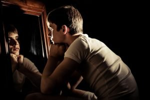 Jugendlicher schaut in den Spiegel