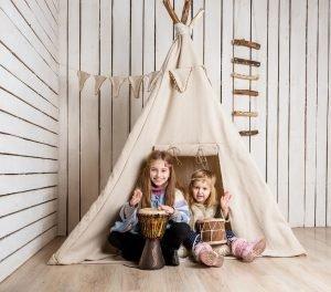 zwei Kinder spielen Indianer in einem Zelt