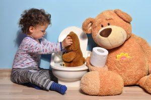 Sauberkeitserziehung Kind setzt Teddy auf Toilette