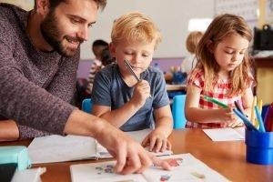 inklusionshelfer hilft einem schueler im klassenzimmer