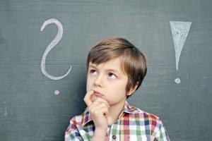 Kind steht vor einer Tafel mit einem Ausrufezeichen sowie einem Fragezeichen