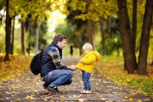 Vater zieht seinem Kind eine Jacke an