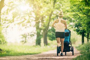 frau joggt mit kinderwagen durch den wald