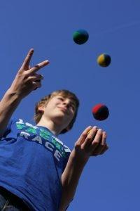 ein kind trainiert seine koordinativen faehigkeiten beim jonglieren