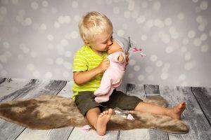 ein kleiner Junge spielt mit einer Puppe
