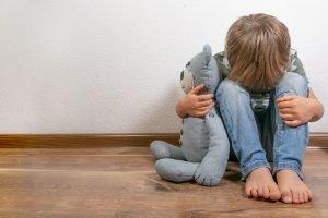 Junge sitzt traurig und verzweifelt mit seinem Teddy am Boden