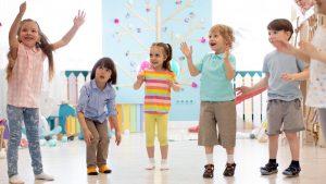 kindergartenkinder stehen in einem halbkreis und ahmen bewegungen nach