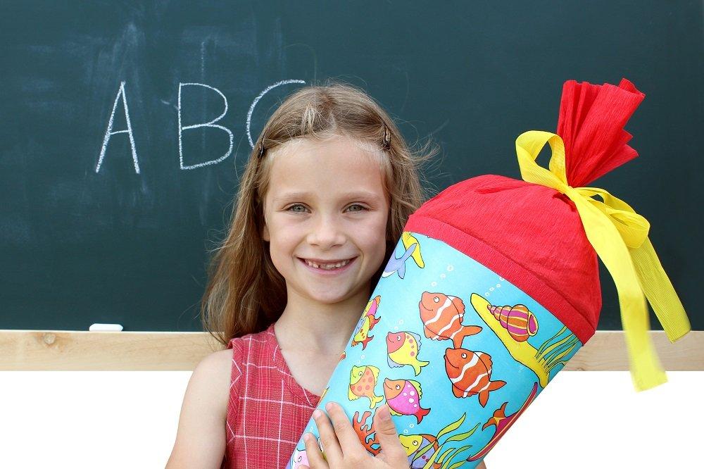Mädchen steht mit Zuckertüte vor Schultafel