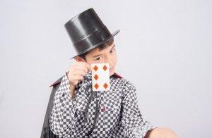 Kind mit Zauberhut zeigt eine Spielkarte