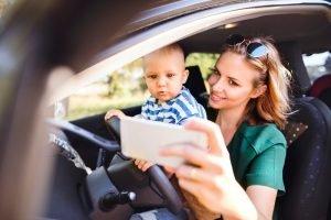Mutter lenkt ihr Kind mit dem Smartphone ab