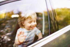 Kind steht am Fenster im Auto